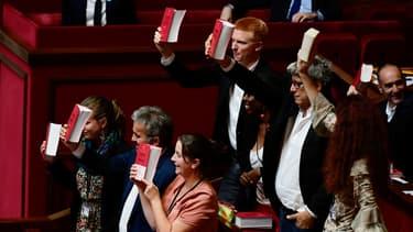 Des députés de la France insoumise brandissent le code du Travail à l'Assemblée nationale.