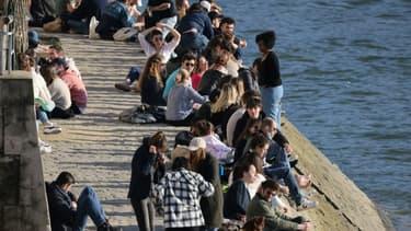 Des personnes se rassemblent le long de la Seine pour profiter d'un après-midi ensoleillé, à Paris, le 28 février 2021