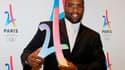 Teddy Riner pose avec le logo de candidature de Paris 2024