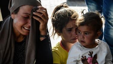 Des proches de victimes des attentats à la voiture piégée commis dans la nuit du 25 juin, à Kobané.
