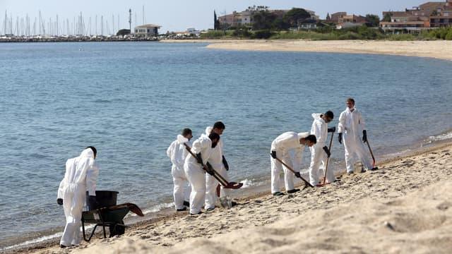 Des pompiers nettoient la plage de Solaro, le 14 juin 2021.