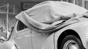 En 1949, un ouvrier repeignant une plaque d'immatriculation d'une voiture au Salon de l'Automobile à Paris. Au Québec, c'est du vernis anti-radar automatique que les automobilistes peuvent asperger sur leurs plaques.