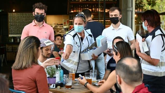 Des médiateurs délivrent du gel hydroalcoolique à des consommateurs le 12 juin 202 à la terrasse d'un bar de Strasbourg après la découverte d'un cluster du variant delta du covid dans une école d'arts de la ville.
