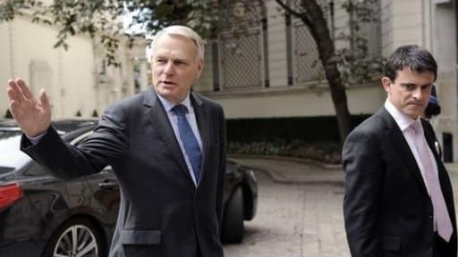 Le Premier ministre Jean-Marc Ayrault (g.) et son ministre de l'Intérieur Manuel Valls dans la cour de Matignon.