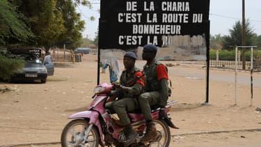 Soldats maliens circulant devant un panneau exaltant la Charia, en 2013.