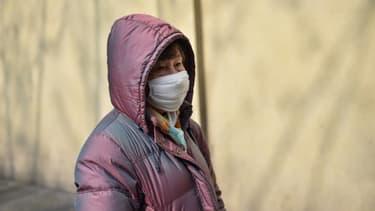 Une femme avec un masque protecteur devant l'hôpital de Huashan à Shanghai, le 21 janvier 2020 en Chine.