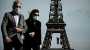 Homme et femme portant un masque devant la Tour Eiffel à Paris (photo d'illustration)