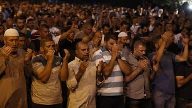 Des musulmans palestiniens prient devant l'enceinte de l'esplanade des mosquées à Jérusalem pour protester contre les contrôles par les autorités israéliennes, le 23 juillet 2017