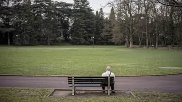 Un homme assis sur un banc du Parc de la Tête d'Or à Lyon en décembre 2012