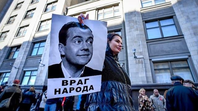 """Une manifestante tenant un portrait de Dmitri Medvedev avec l'inscription """"Ennemi du peuple""""."""