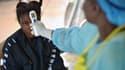 La température d'une jeune fille, suspectée d'être infectée par le virus Ebola, est contrôlée dans un hôpital de Sierra Leone, le 16 août2014.
