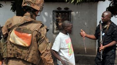 Un soldat français de l'opération Sangaris et un gendarme centrafricain confisquent un couteau à un homme, à Bangui le 9 février.