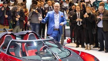 Christian von Koenigsegg, en costume bleu, en pleine présentation d'un nouveau modèle sur son stand, au salon automobile de Genève le 7 mars.