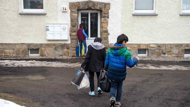 De jeunes demandeurs d'asile en provenance de Syrie entrent dans le centre de réfugiés où ils sont logés, à Clausnitz en Allemagne de l'Est, le 2 mars 2016. (Photo d'illustration)