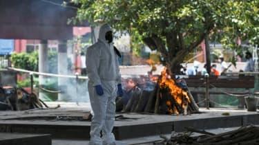 Vêtu d'une combinaison de protection, un proche d'une personne décédée du coronavirus se recueille durant la crémation, le 3 juin 2020 au Nigambodh Ghat à New Delhi