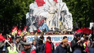 """Gilets jaunes et syndicalistes à Paris le 27 avril, auprès d'une pancarte reprenant """"La liberté guidant le peuple"""", d'Eugène Delacroix."""