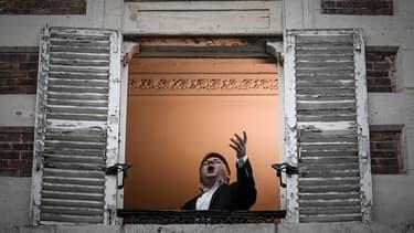 Le chanteur lyrique Stéphane Sénéchal à la fenêtre de son appartement à Paris, le 26 mars 2020