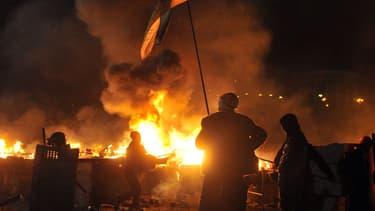 Des manifestants font face à la police, mardi soir, à Kiev, sur la place de l'Indépendance en flammes.