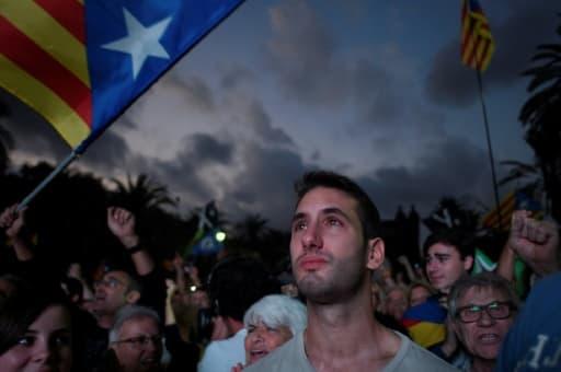 Des partisans de l'indépendance de la Catalogne écoutent le discours de Carles Puigdemont diffusé sur un écran devant l'Arc de Triomphe de Barcelone, le 10 octobre 2017