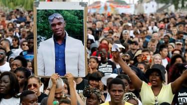 Portrait d'Adama Traoré brandi lors d'une manifestation le 21 juillet 2018 à Beaumont-sur-Oise, deux ans après sa mort