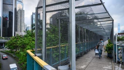 Un habitant de Hong Kong emprunte le 3 juin 2020 une passerelle recouverte de grillage, édifiée par les autorités locales en réponse aux manifestations pro-démocratie.