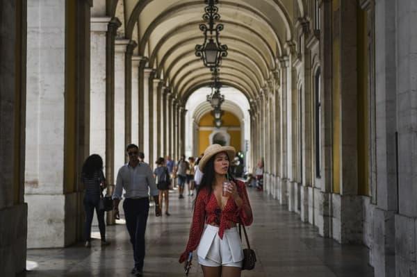 Une femme se promène dans les arcades ombragées de Lisbonne au Portugal, où la caleur a atteint des records ces derniers jours.