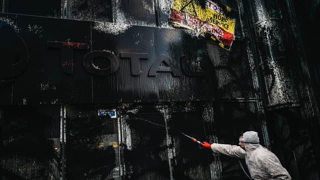 Des militants d'Attac repeignent en noir le siège de Total.