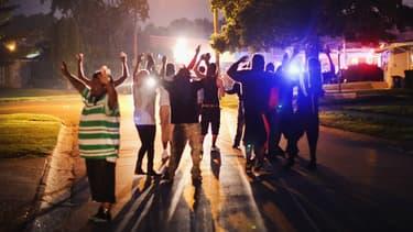 Proches de Michael Brown rassemblés dans son quartier, lundi soir à Ferguson, dans l'Etat du Missouri.