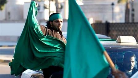 Un partisan de Mouammar Kadhafi dans un cortège de voitures dans le centre de Tripoli. Des tirs ont retenti dimanche avant l'aube dans la capitale libyenne, où la télévision publique, citant une source militaire, affirme que les forces régulières ont repr