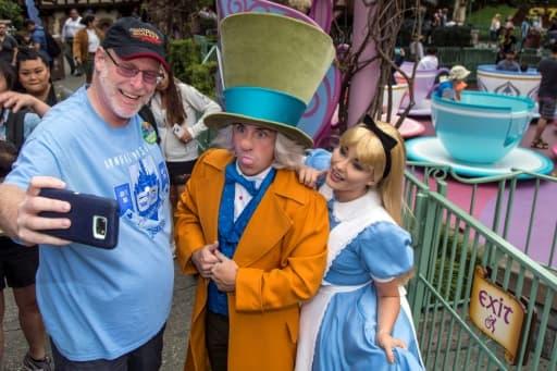 Photo fournie par Disney de Jeff Reitz en compagnie d'Alice et du Chapelier fou, le 22 juin 2017 lors de sa 2.000ème visite du parc d'attractions Disneyland à Anaheim (Los Angeles)