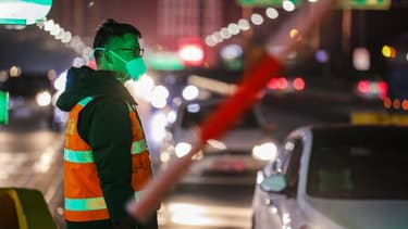 Un membre des forces de sécurité près d'une autoroute de Wuhan, en Chine.