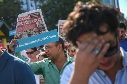 """Un journaliste de Cumhuriyet brandit une pancarte avec le slogan """"le journalisme n'est pas un crime"""", le 24 juillet 2017 devant le tribunal d'Istanbul"""