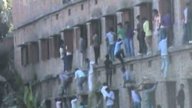 Des dizaines de personnes en train d'escalader les murs d'un centre scolaire dans l'Etat de Bihar en Inde