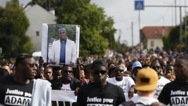 Des manifestants lèvent un portrait d'Adama Traoré en son hommage, en juillet 2018 à Beaumont-sur-Oise. FRANCOIS GUILLOT / AFP