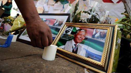 Un homme enflamme une bougie près des portraits de Nelson Mandela devant la clinique de Pretoria, le 11 juillet 2013.