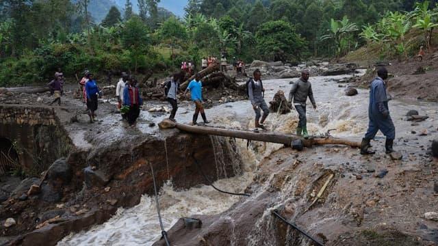 Des habitants traversent la rivière, une journée après l'immense glissement de terrain qui a eu lieu à l'est de l'Ouganda.