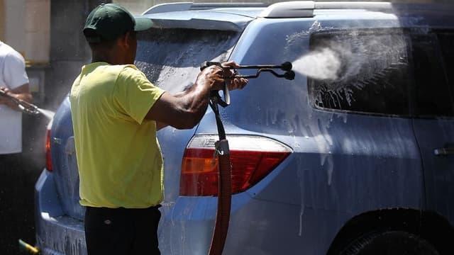 Un homme en train de laver son véhicule (Photo d'illustration).