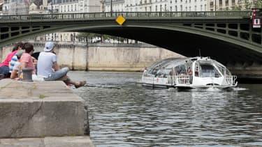 Les touristes regardent un bateau-mouche sur la Seine, à Paris, le 9 juin 2014.