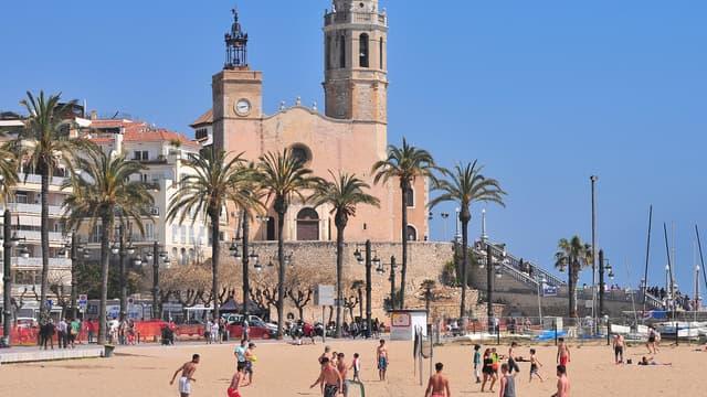 Des jeunes gens en train de jouer au beach volley sur une plage de Sitges, près de Barcelone.