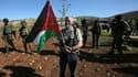 Un homme tient un drapeau palestinien et un olivier lors d'une manifestation destinée à planter 300 oliviers dans le village de Turmus Aya, près de Ramallah, dans un territoire occupé par Israël, le 10 Décembre 2014. (Illustration)