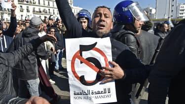 """Un manifestant brandit une pancarte avec un """"5"""" barré et une inscription """"Non au 5e mandat"""" d'Abdelaziz Bouteflika, le 22 février 2019 à Alger."""