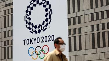 Un piéton passe devant le logo officiel des Jeux olympiques 2020 à Tokyo le 7 avril 2021