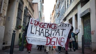 """Des habitants de Marseille brandissent une pancarte """"L'urgence c'est l""""habitat digne"""", le 5 novembre 2018 après l'effondrement des bâtiments de la rue d'Aubagne."""
