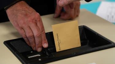 Un électeur glisse son bulletin de vote dans l'urne (illustration)