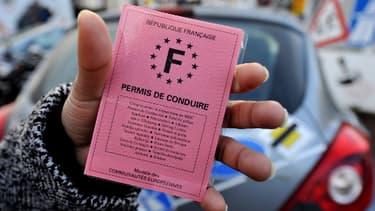 Une jeune femme montre son permis de conduire. Image d'illustration.