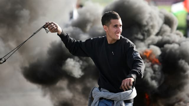 Un manifestant palestinien prêt à lancer une pierre contre les soldats israéliens, près du checkpoint de Jamala, le 24 février 2013.