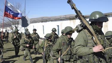 Un homme portant le drapeau russe salue des militaires en treillis qui bloquent l'accès à une base de la frontière ukrainienne à Perelvane, non loin de Simpferopol, le 3 mars 2014.