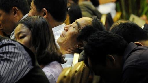 Yan Jiacheng, au centre, avec d'autres proches des disparus du vol MH370, dans un hôtel à Pékin le 23 avril.