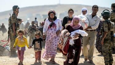 Des Kurdes de Syrie fuyant les jihadistes de l'Etat islamique passent la frontière turque, le 20 septembre 2014.