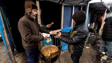 """Un bénévole distribue de repas sur le site de la """"Jungle"""" de Calais."""